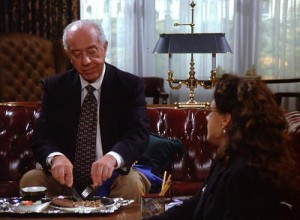 Ian Abercrombie as Mr. Pitt in Seinfeld eating a chocolate bar with a fork and knife