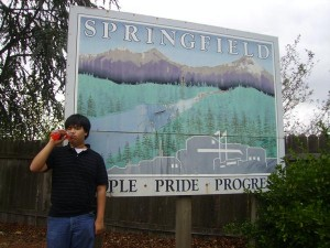 Nik Choeychan in front of the Springfield, Oregon sign