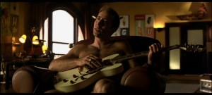 Nicholas Cage as Stanley Goodspeed, naked and playing the guitar, in the Rock